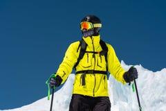 Skidåkareanseende på en lutning Mannen i en ljus dräkt, hjälmen och maskering i skidåkning ska skida I denkorkade bakgrunden arkivfoto