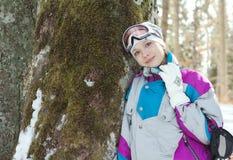 Skidåkarekvinnaanseende nära stammen av ett träd i vinterskog Arkivbild