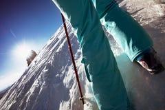 Skidåkaren går stigande till snöberget Arkivbild