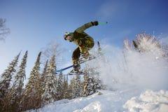 Skidåkaren hoppar från en språngbräda i skidasemesterorten Arkivbilder