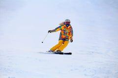 Skidåkaren i maskeringsglidbanor fastar, medan skida från lutning arkivfoton