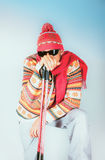 Skidåkaren i stucken ullprydnadklänning med skidar poler och sunglass arkivfoton
