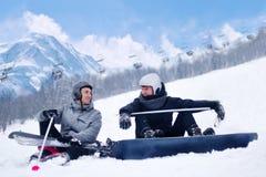 Skidåkaren och snowboarderen efter att ha skidat och snowboarding vilar, sitter samtalet, skratt mot bakgrunden av berg Skida och Royaltyfria Bilder