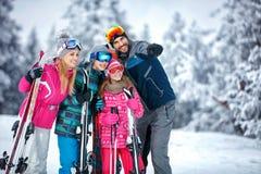 Skidåkning, vinter, snö, sol och gyckel - familj som tycker om ferievaca arkivbilder