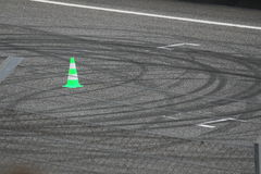 Skid marks on a race track tarmac. A green pin in a rece track full of skid marks Stock Photography