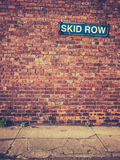 Skid Row Sign On Brick Wall. Urban Decay Image Of A Skid Row Sign On A Red Brick Wall Stock Image