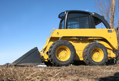 Skid Steer - facing left. A parked Skid Steer on dried grass Stock Photos