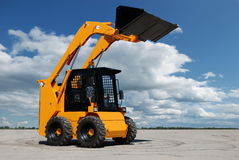 Skid steer loader. With full raised bucket outdoors Stock Photography