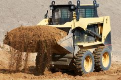 Skid steer loader at earth moving works. Skid steer loader moving sand soil at construction area outdoors Stock Images