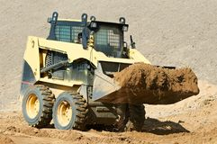 Skid steer loader at earth moving works. Skid steer loader moving sand soil at construction area outdoors Royalty Free Stock Photography