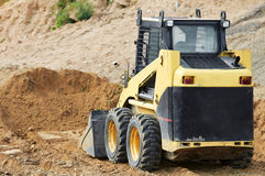 Skid steer loader at earth moving works. Skid steer loader moving sand soil at construction area outdoors Royalty Free Stock Image