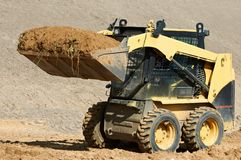 Skid steer loader at earth moving works. Skid steer loader moving sand soil at construction area outdoors Stock Photography