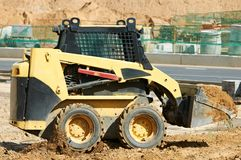 Skid steer loader at earth moving works. Skid steer loader moving sand soil at construction area outdoors Stock Photos