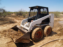 Skid Steer Loader - Horizontal. Construction worker driving a skid steer loader at a desert construction site. Horizontally framed shot Royalty Free Stock Image