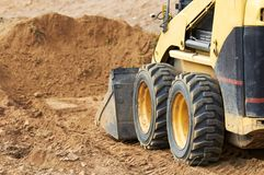 Skid steer loader works. Closeup skid steer loader excavator at road construction work Stock Photography