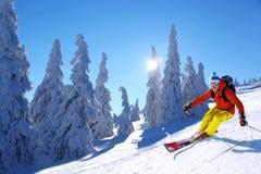 Skida för skidåkare som är sluttande i höga berg mot solnedgång Fotografering för Bildbyråer