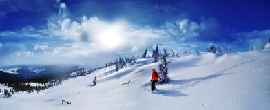 Skida för skidåkare som är sluttande i höga berg mot solnedgång arkivfoto