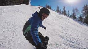 Skida i fjällängarna i vintern En man rullar på en snowboard på detäckte slingorna av en bergsemesterort _ lager videofilmer