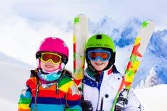 Skida och snöa gyckel för ungar i vinterberg Royaltyfri Bild