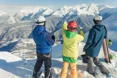 skida snowboarden Sportkvinna och man i snöig berg Arkivfoto