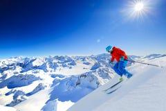 Skida turnera mannen som når överkanten i schweiziska fjällängar royaltyfria bilder