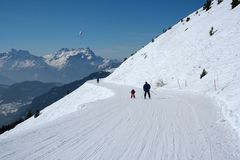 , Skidar övervintrar, snöfamiljen som tycker om vintersemester i Verbier, Schweiz royaltyfri bild