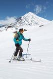 Skidar bergsbestigaren som klättring skidar på på bakgrundsvulkan Royaltyfri Foto