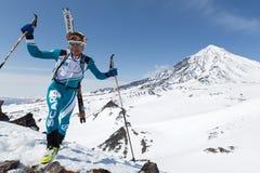 Skidar bergsbestigaren som klättring till berget på bakgrundsvulkan med skidar fastspänt för att vandra Royaltyfri Foto