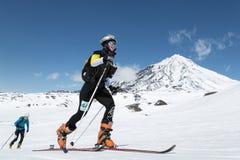 Skidar bergsbestigning: flickan skidar bergsbestigaren som klättring skidar på på bakgrundsvulkan Arkivbilder