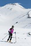 Skidar bergsbestigning: kvinnan skidar bergsbestigareritter som skidar från vulkan Arkivfoton