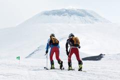 Skidar bergsbestigning: två skidar bergsbestigaren som löneförhöjningen till vulkan skidar på Arkivfoton
