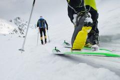 Skidar bergsbestigningkängadetaljen under stigning i snön arkivfoton