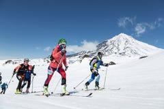 Skidar bergsbestigningmästerskap: gruppen skidar bergsbestigaren som klättring skidar på på bakgrundsvulkan Royaltyfria Foton