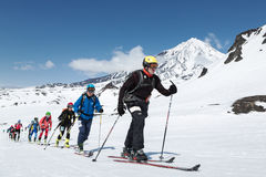 Skidar bergsbestigningmästerskap: gruppen skidar bergsbestigaren som klättring skidar på på bakgrundsvulkan Fotografering för Bildbyråer