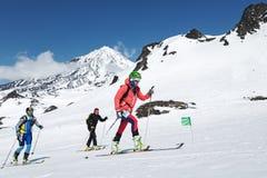 Skidar bergsbestigningmästerskap: gruppen skidar bergsbestigaren som klättring skidar på på bakgrundsvulkan Arkivbilder