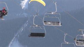 Skidar hissen med en paragliding på bakgrunden arkivfilmer