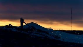 Skidar hopp- och stolelevatorn med orange solnedgångtidschackningsperiod arkivfilmer