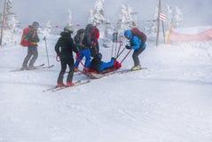 Skidar kommer med räddningsmanskapet med glidbanabåren, hjälp royaltyfri bild