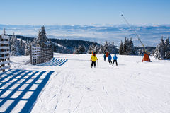 Skidar lutningen, folket som skidar ner kullen, bergsikt Royaltyfri Foto