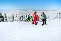 Skidar lutningen, folket som skidar ner kullen, bergsikt Royaltyfri Bild