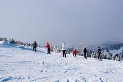 Skidar lutningen, folket som skidar ner kullen, bergsikten, dimma Arkivbild