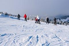 Skidar lutningen, folket som skidar ner kullen, bergsikten, dimma Royaltyfria Foton