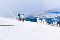 Skidar lutningen, folket som skidar ner kullen, bergsikten, dimma Arkivfoto