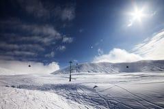 Skidar lutningen, gondolelevatorn och blå himmel med solen Royaltyfri Fotografi