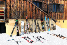 Skidar och snowboards på snön mot alpin chalet Arkivfoton
