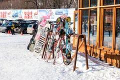 Skidar, och snowboards står på kuggarna Arkivfoton