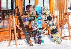 Skidar, och snowboards står på kuggarna Royaltyfri Foto