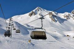 Skidar semesterorten med kabelbilar eller den flyg- elevatorn och skidlift som flyttar ab arkivfoto