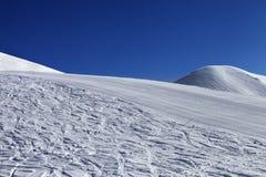 Skidar slösar lutningen och klar himmel i trevlig dag Arkivbild