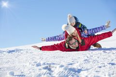 , Skidar snösolen och gyckel - den lyckliga familjen skidar på ferie royaltyfria foton